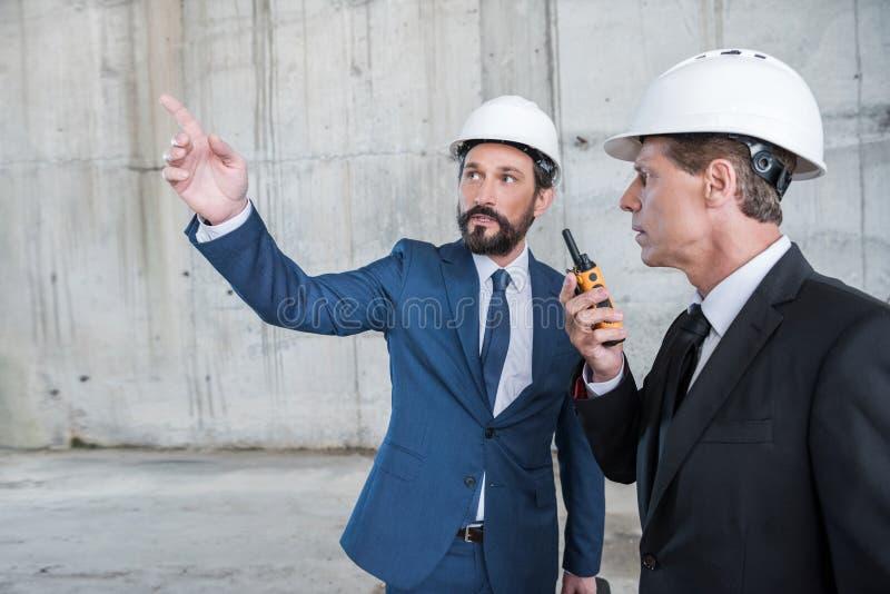 Αρχιτέκτονες hardhats χρησιμοποιώντας walkie-talkie και συζητώντας το πρόγραμμα στο εργοτάξιο οικοδομής στοκ εικόνες