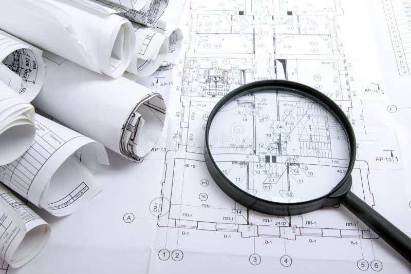 Αρχιτεκτονικά σχεδιαγράμματα, ρόλοι σχεδιαγραμμάτων και ενίσχυση - γυαλί στο άσπρο υπόβαθρο στοκ εικόνες