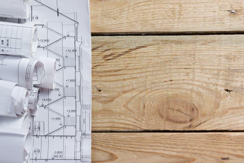 Αρχιτεκτονικοί σχεδιαγράμματα και ρόλοι σχεδιαγραμμάτων στο ξύλινο υπόβαθρο στοκ εικόνες