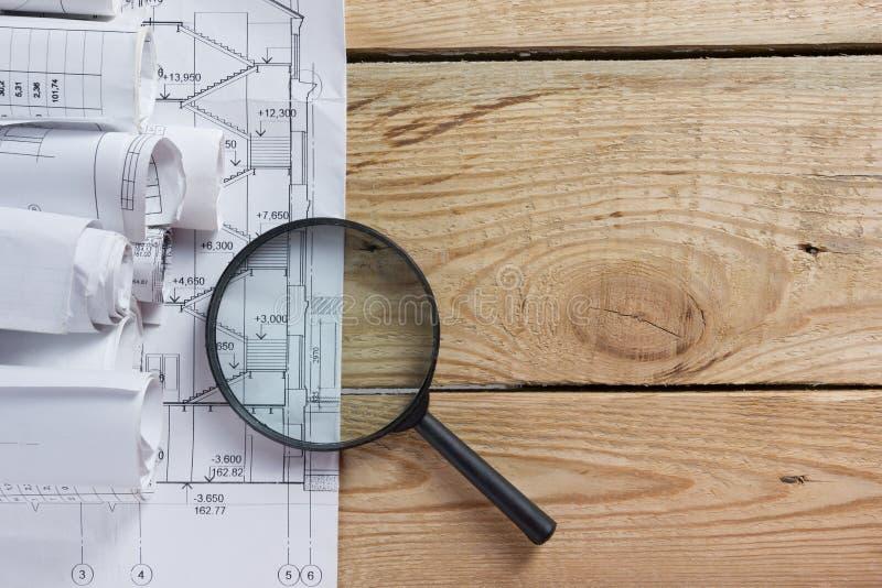 Αρχιτεκτονικοί σχεδιαγράμματα και ρόλοι σχεδιαγραμμάτων στο ξύλινο υπόβαθρο στοκ φωτογραφία με δικαίωμα ελεύθερης χρήσης