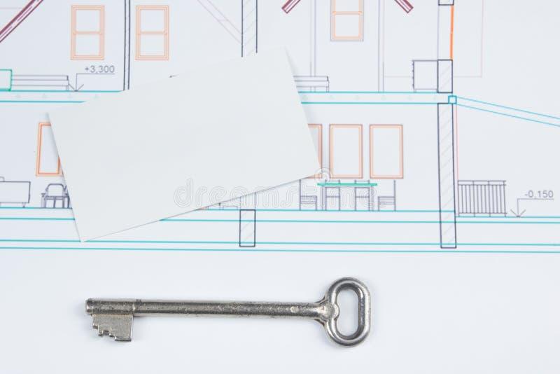 Αρχιτεκτονικό πρόγραμμα, σχεδιαγράμματα, κλειδί με τον αριθμό σπιτιών και κενή επαγγελματική κάρτα στο ξύλινο υπόβαθρο τα επίπεδα στοκ φωτογραφία με δικαίωμα ελεύθερης χρήσης