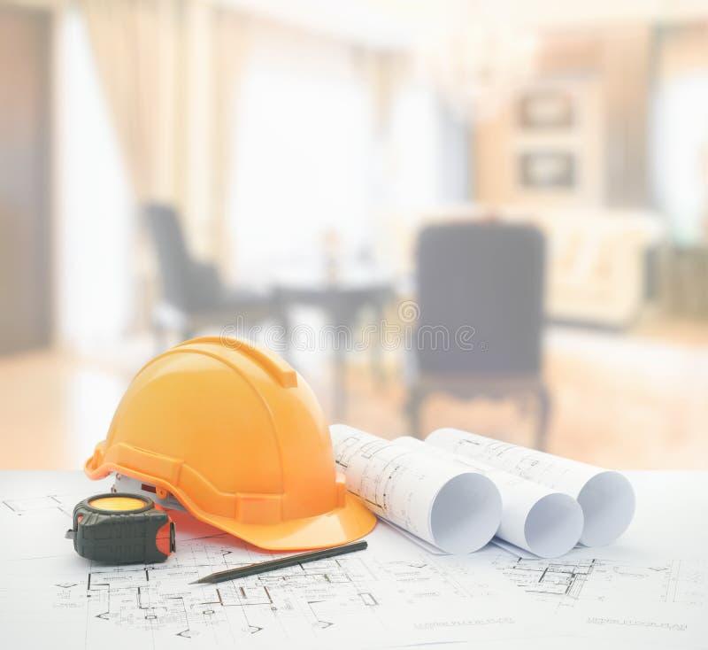 Αρχιτεκτονικό σχεδιάγραμμα με το κράνος ασφάλειας και εργαλεία πέρα από το κλασικό καθιστικό στοκ εικόνα