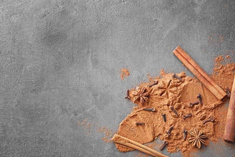 Αρωματικά ραβδιά κανέλας, σκόνη και καρυκεύματα στο γκρίζο υπόβαθρο στοκ φωτογραφία