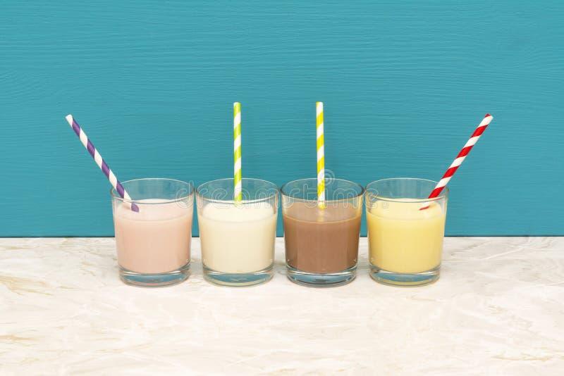 Αρωματικός milkshakes και γάλα με τα άχυρα στους ανατροπείς γυαλιού στοκ εικόνα