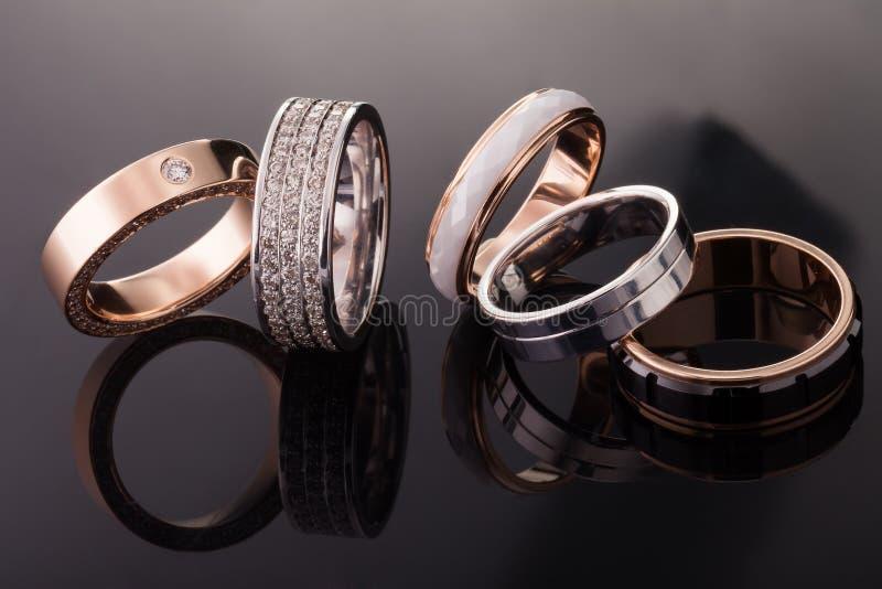 Ασήμι, χρυσός, δαχτυλίδια λευκόχρυσου των διαφορετικών μορφών στο σκοτεινό υπόβαθρο των αντανακλάσεων στοκ φωτογραφία με δικαίωμα ελεύθερης χρήσης