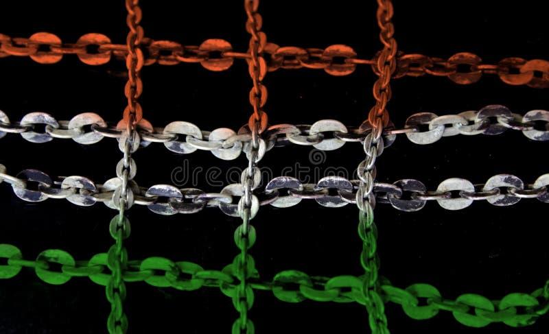 Ασημένια αλυσίδα στο σταυρωτό χρωματισμένο σχέδιο πορτοκάλι και πράσινος στοκ φωτογραφίες με δικαίωμα ελεύθερης χρήσης