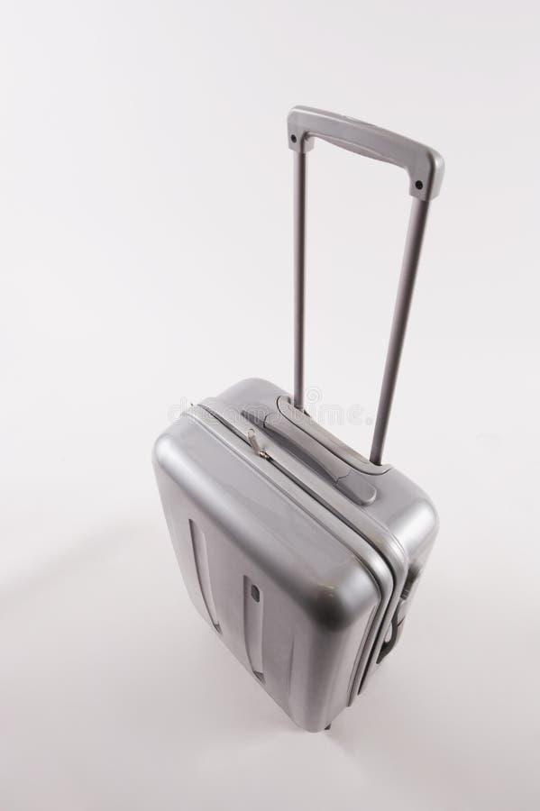 Ασημένια βαλίτσα με τη μακριά λαβή στο άσπρο κλίμα στοκ φωτογραφία με δικαίωμα ελεύθερης χρήσης