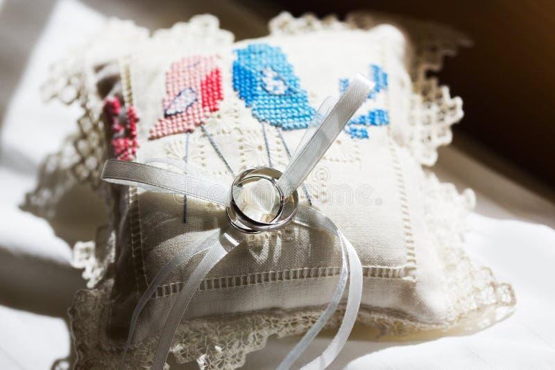 Ασημένια γαμήλια δαχτυλίδια στο άσπρο χειροποίητο μαξιλάρι με δύο πουλιά φιλήματος στοκ εικόνα