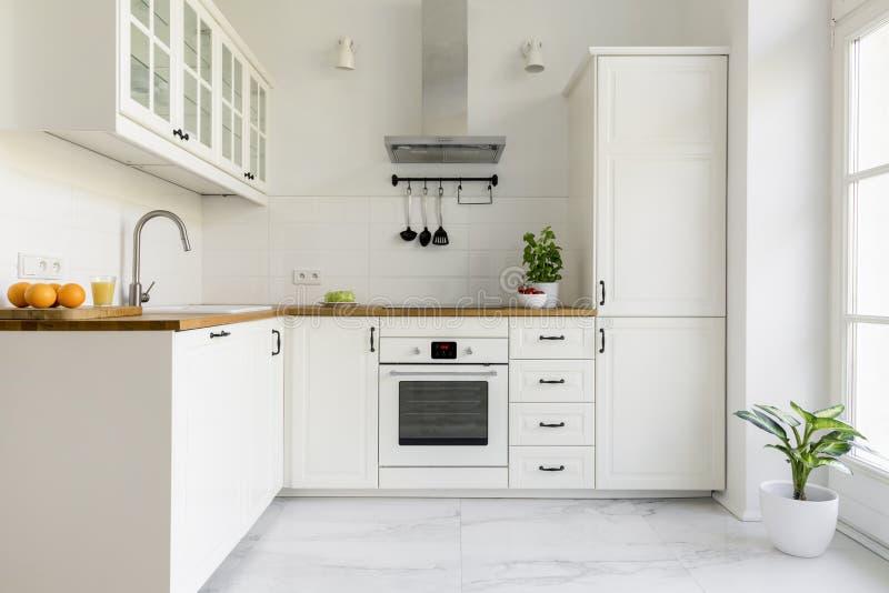 Ασημένια κουκούλα κουζινών στο ελάχιστο άσπρο εσωτερικό κουζινών με τις εγκαταστάσεις στοκ φωτογραφίες