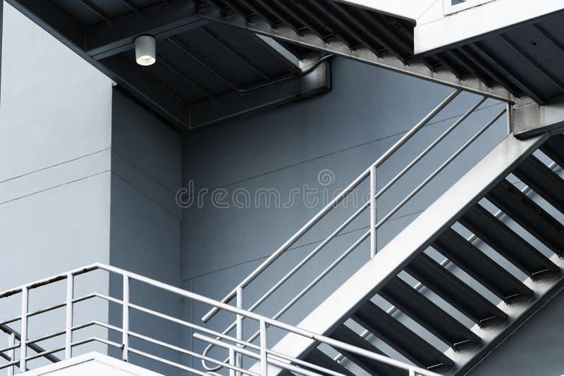 Ασημένια σκαλοπάτια έκτακτης ανάγκης στο γκρίζο κτήριο στοκ φωτογραφία