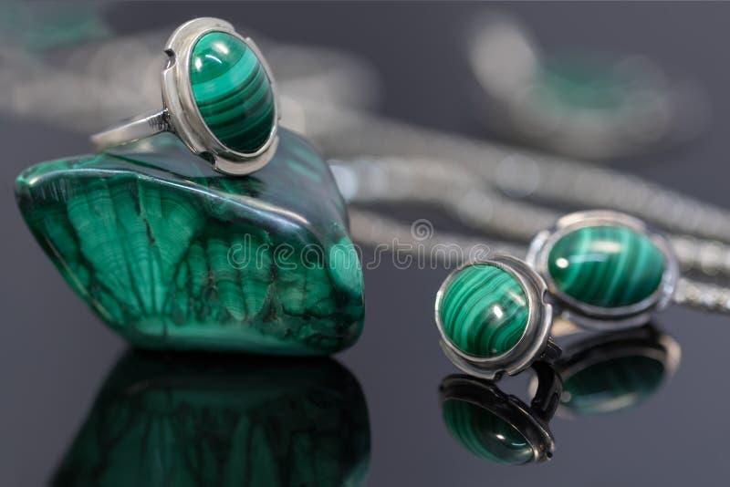 Ασημένια σκουλαρίκια και δαχτυλίδι κινηματογραφήσεων σε πρώτο πλάνο με malachite πάνω από malachite το κομμάτι πετρών στο υπόβαθρ στοκ εικόνες