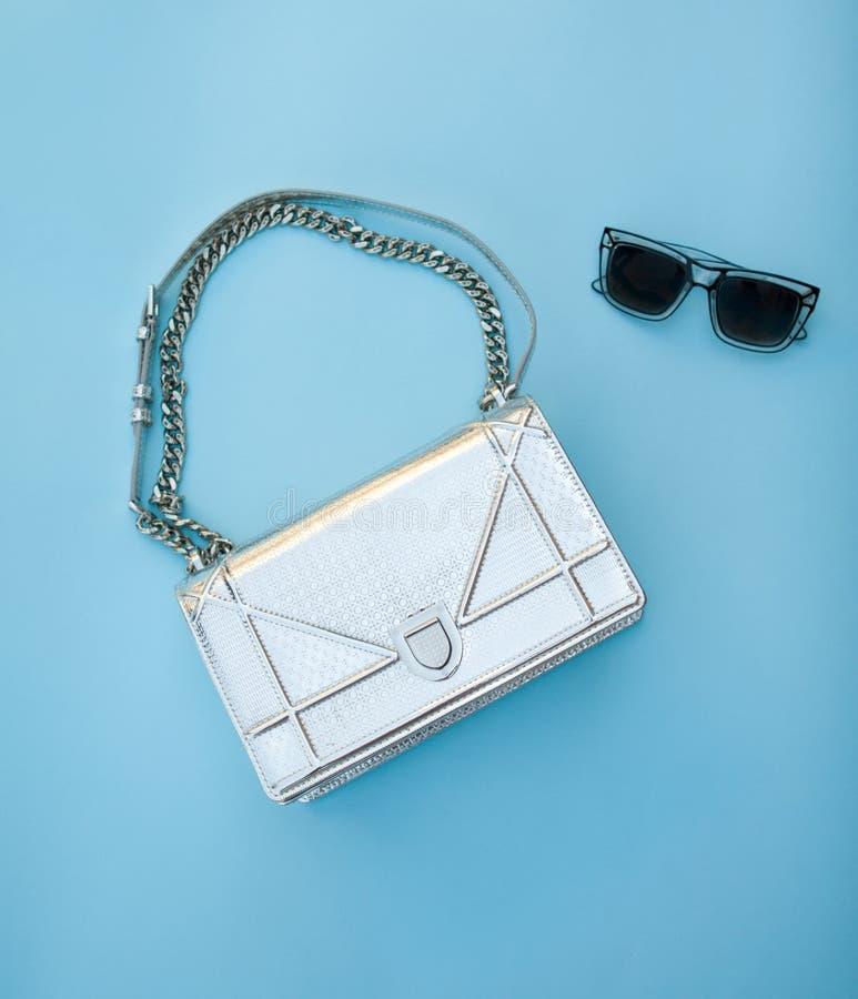 Ασημένια τσάντα με τα μαύρα γυαλιά σε ένα μπλε υπόβαθρο στοκ εικόνα