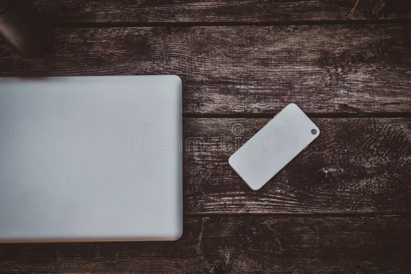 Ασημένια lap-top, smartphone και thermos στον ξύλινο πίνακα στοκ εικόνα