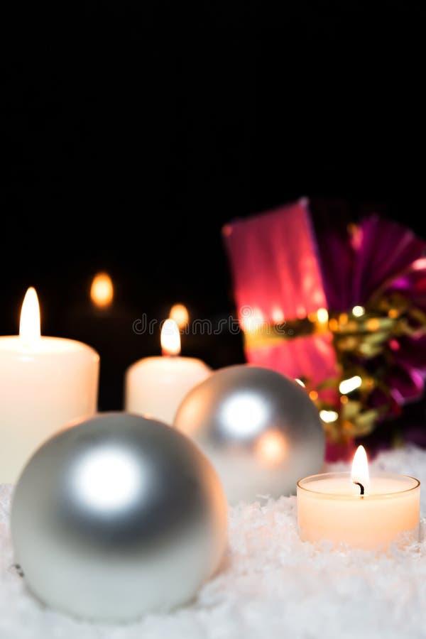 Ασημένιες σφαίρες Χριστουγέννων, κεριά και ένα κόκκινο δώρο στο χιόνι στοκ φωτογραφία με δικαίωμα ελεύθερης χρήσης