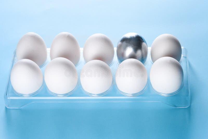 Ασημένιο αυγό σε ένα πλαστικό κιβώτιο με τα άσπρα αυγά Ηγεσία, μοναδικότητα, ανεξαρτησία, νέα ιδέα, έννοια πρωτοβουλίας στοκ φωτογραφία με δικαίωμα ελεύθερης χρήσης