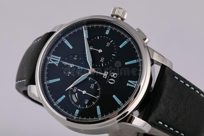 Ασημένιο ρολόι ατόμων με έναν μαύρο πίνακα, μπλε δεξιόστροφα, chronograph, χρονόμετρο με διακόπτη, με ένα μαύρο λουρί δέρματος με στοκ εικόνες με δικαίωμα ελεύθερης χρήσης