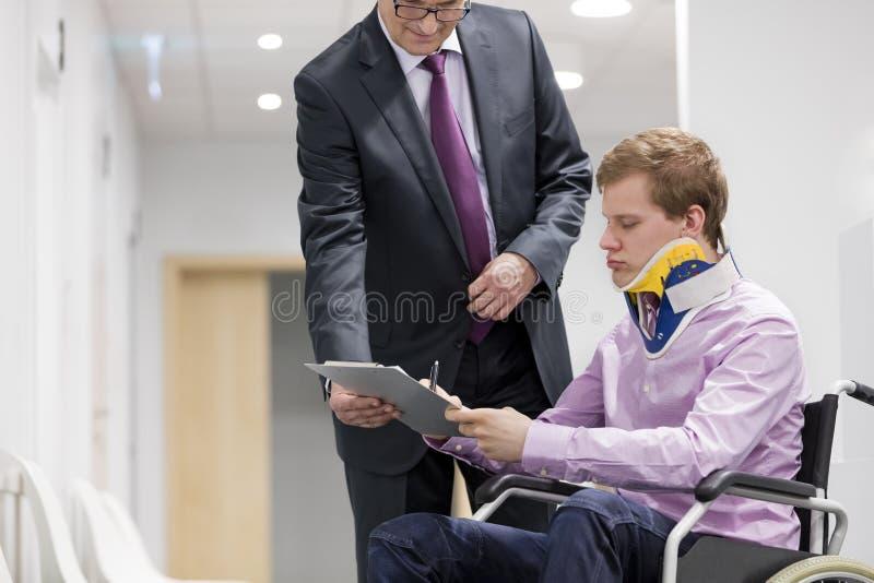 Ασθενής με το στήριγμα στο λαιμό που υπογράφει τα έγγραφα από το γιατρό στοκ εικόνες με δικαίωμα ελεύθερης χρήσης
