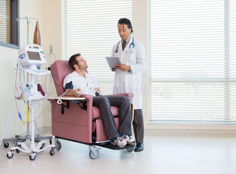 Ασθενής που εξετάζει το γιατρό που χρησιμοποιεί την ψηφιακή ταμπλέτα μέσα στοκ εικόνες με δικαίωμα ελεύθερης χρήσης