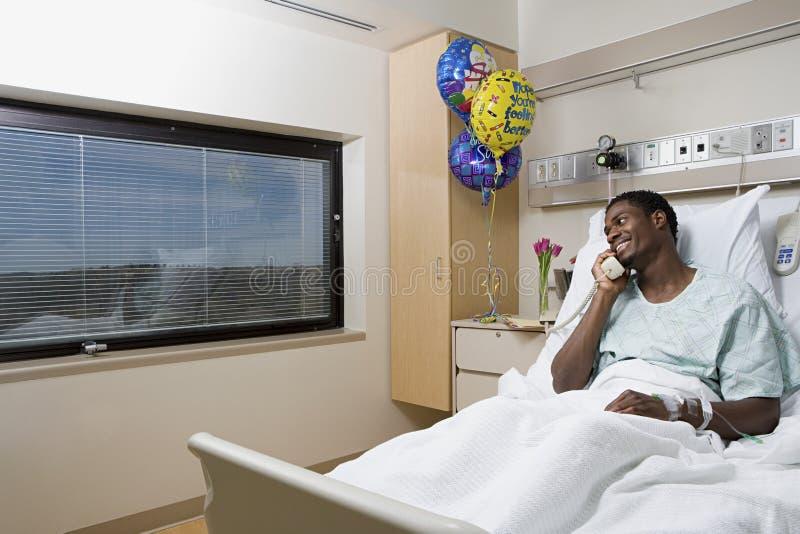 Ασθενής στο τηλέφωνο στο νοσοκομειακό κρεβάτι στοκ εικόνες