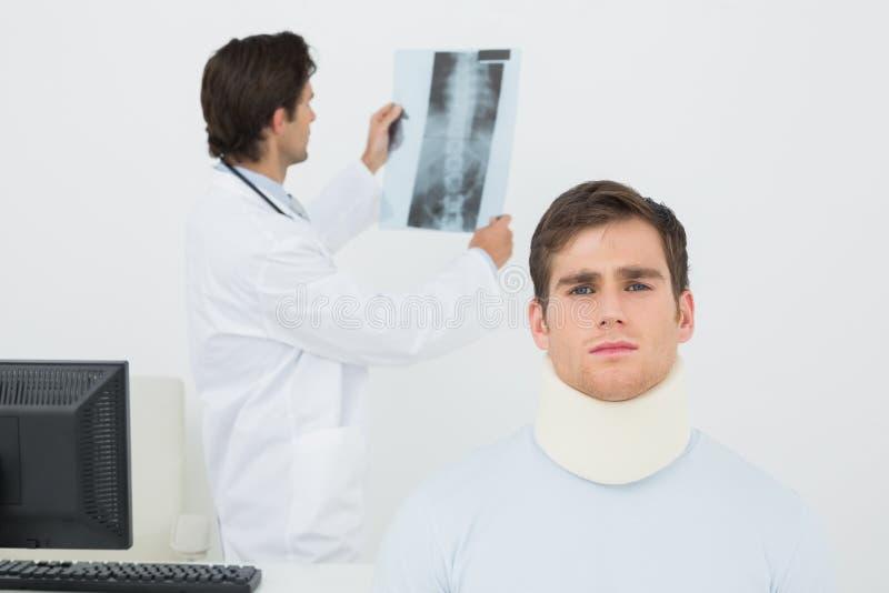 Ασθενής στο χειρουργικό περιλαίμιο με το γιατρό που εξετάζει την ακτίνα X σπονδυλικών στηλών πίσω στοκ φωτογραφία με δικαίωμα ελεύθερης χρήσης