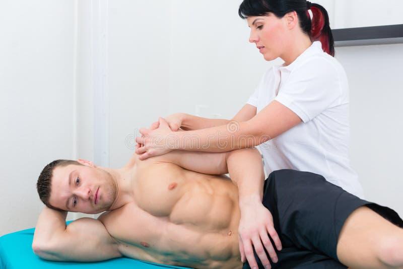 Ασθενής φυσιοθεραπευτών ή αθλητικών γιατρών στην πράξη στοκ εικόνες