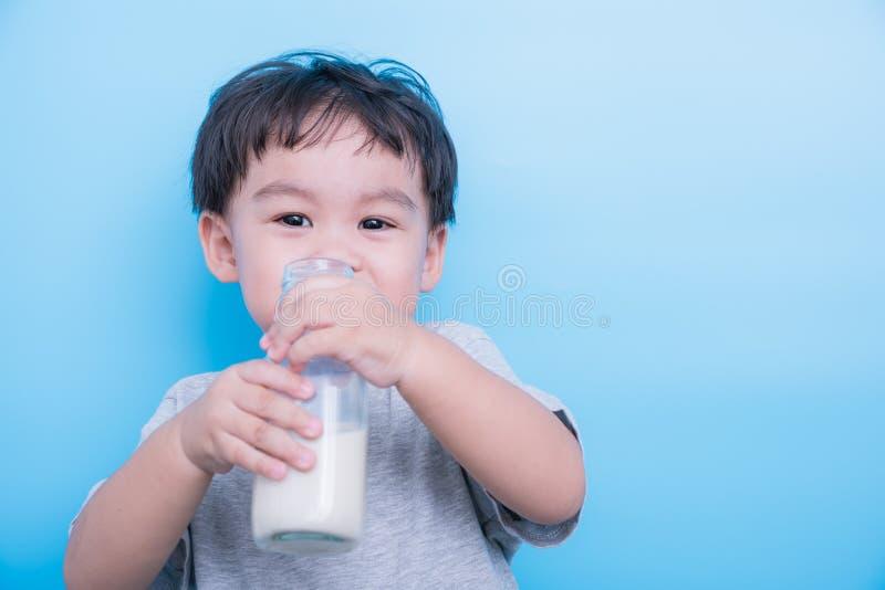 Ασιάτης λίγο πόσιμο γάλα αγοράκι από το γυαλί μπουκαλιών στο μπλε υπόβαθρο στοκ εικόνα με δικαίωμα ελεύθερης χρήσης