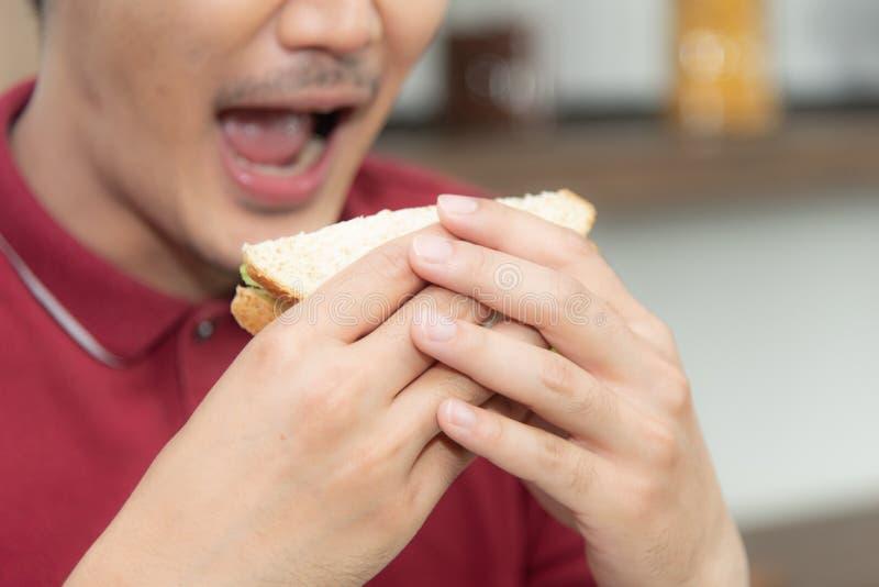 Ασιάτης που χαμογελά το νεαρό άνδρα με την περιστασιακή κόκκινη μπλούζα enyoy έχοντας το πρόγευμα, που τρώει το σάντουιτς, τα μαγ στοκ εικόνα με δικαίωμα ελεύθερης χρήσης