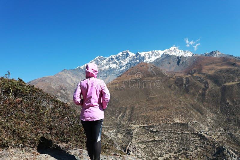 Ασιάτισσα τρέκερ στην κοιλάδα του στρατοπέδου του Έβερεστ, πεζοπορία στο Khumbu, Νεπάλ με χιόνι στο βάθος στοκ εικόνες