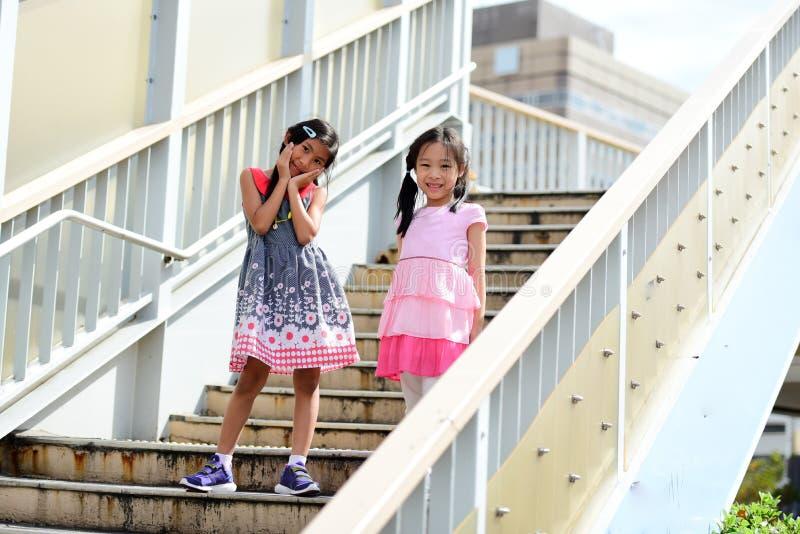 Ασιατικά κορίτσια που στέκονται και που περπατούν στα σκαλοπάτια στοκ φωτογραφία