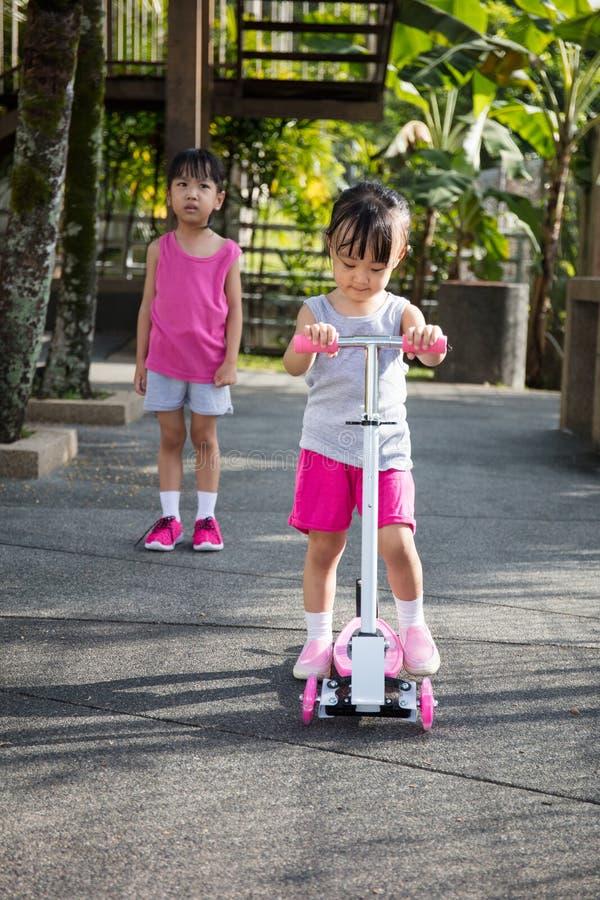 Ασιατικά μικρά κινεζικά κορίτσια που υποστηρίζουν για να παίξει το μηχανικό δίκυκλο στοκ φωτογραφία με δικαίωμα ελεύθερης χρήσης