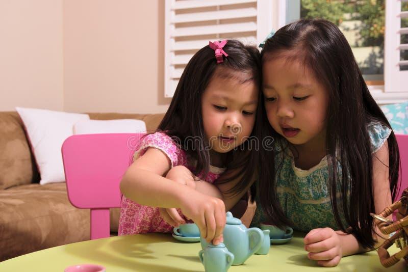 Ασιατικά μικρά παιδιά που παίζουν με το σύνολο τσαγιού στοκ φωτογραφία με δικαίωμα ελεύθερης χρήσης