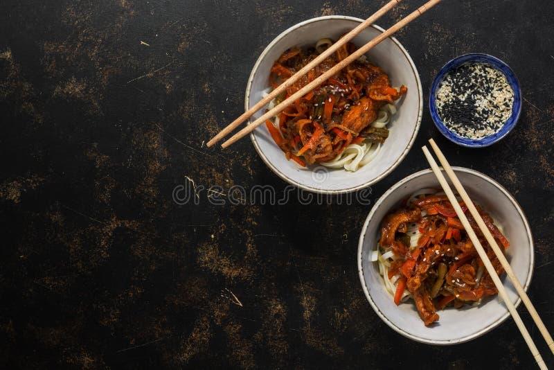 Ασιατικά νουντλς udon με τη σάλτσα teriyaki κοτόπουλου σε ένα σκοτεινό υπόβαθρο Η τοπ άποψη, επίπεδη βάζει, αντιγράφει το διάστημ στοκ εικόνες