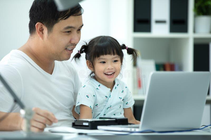 Ασιατικά οικογένεια και μικρό κορίτσι, ενώ ο μπαμπάς εργάζεται με το σημειωματάριο στο W στοκ φωτογραφίες