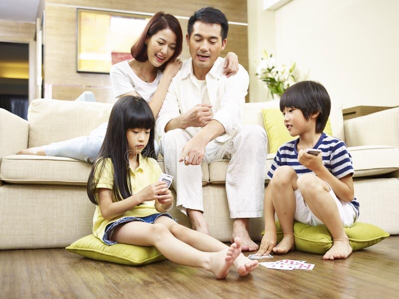 Ασιατικά παιδιά που παίζουν τις κάρτες προσέχοντας γονέων στοκ φωτογραφία με δικαίωμα ελεύθερης χρήσης
