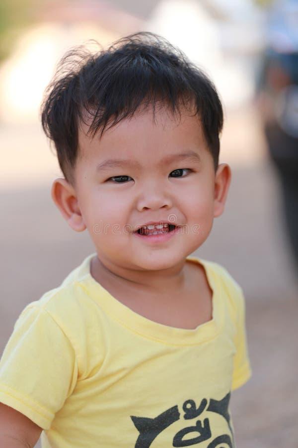 Ασιατικά παιδιά ενός αγοριού σε ένα κίτρινο πουκάμισο και το χαμόγελο ευτυχώς στοκ φωτογραφία με δικαίωμα ελεύθερης χρήσης