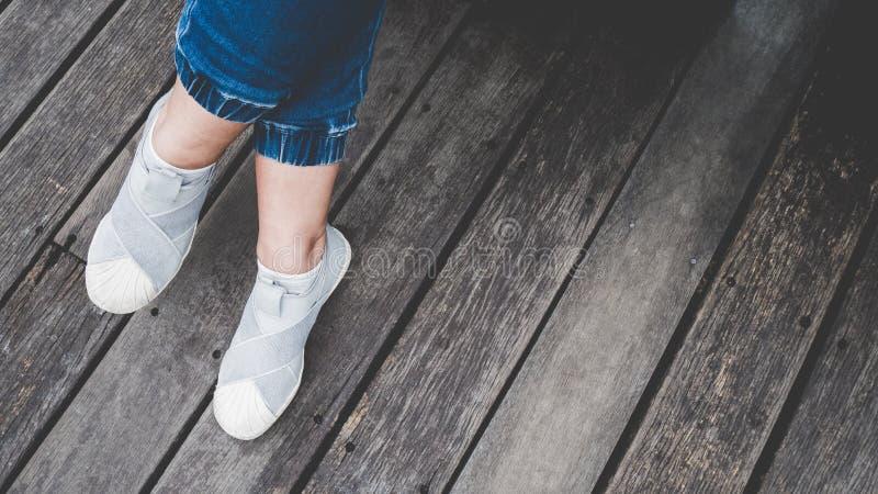 Ασιατικά πόδι και πόδια κοριτσιών που βλέπουν άνωθεν selfie με το τζιν παντελόνι που προετοιμάζεται να ταξιδεψει στοκ φωτογραφία