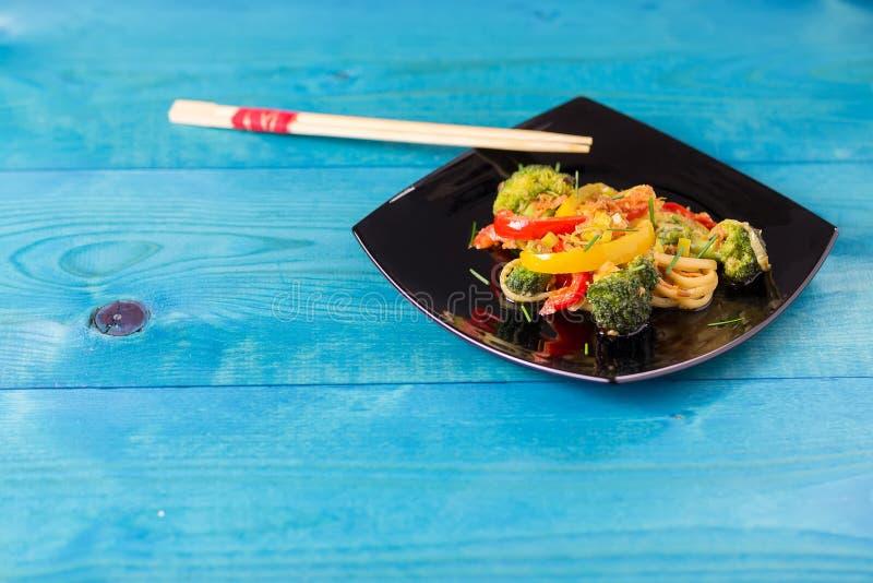 ασιατικά τρόφιμα Ανακατώστε τα νουντλς τηγανητών udon με τα λαχανικά σε ένα μαύρο πιάτο, μπλε ξύλινο backgound, που μαγειρεύεται  στοκ φωτογραφίες