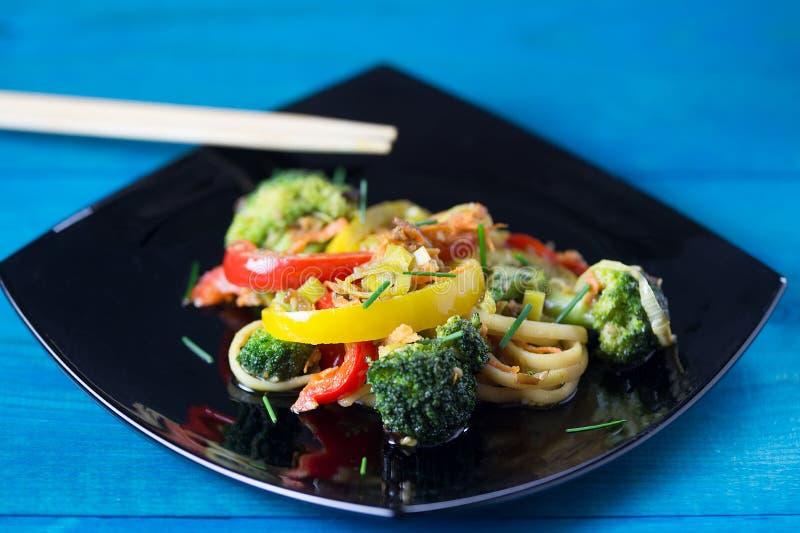ασιατικά τρόφιμα Ανακατώστε τα νουντλς τηγανητών udon με τα λαχανικά σε ένα μαύρο πιάτο, μπλε ξύλινο backgound, που μαγειρεύεται  στοκ εικόνα με δικαίωμα ελεύθερης χρήσης