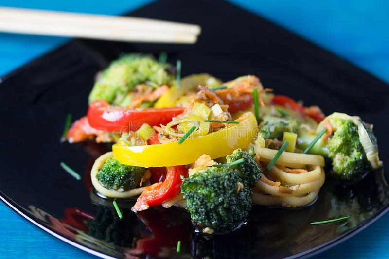 ασιατικά τρόφιμα Ανακατώστε τα νουντλς τηγανητών udon με τα λαχανικά σε ένα μαύρο πιάτο, μπλε ξύλινο backgound, που μαγειρεύεται  στοκ εικόνες