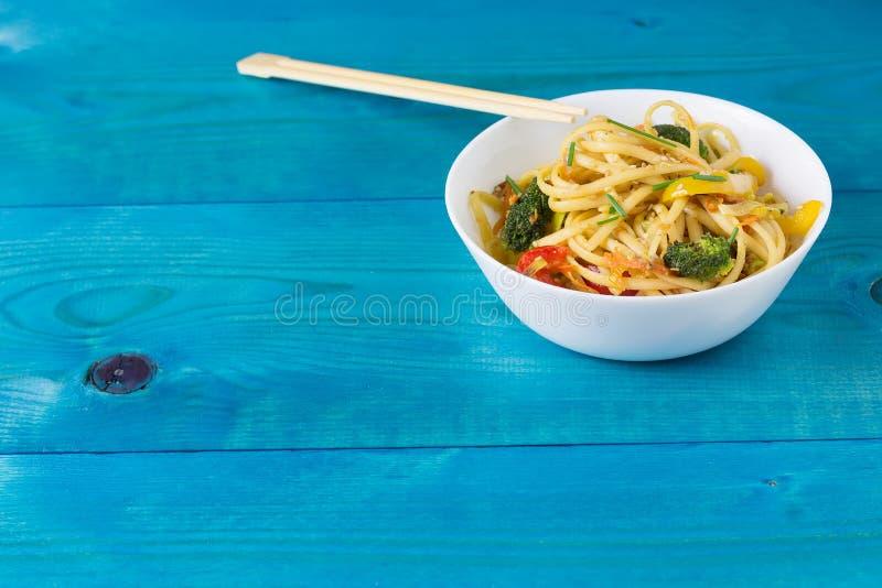ασιατικά τρόφιμα Ανακατώστε τα νουντλς τηγανητών udon με τα λαχανικά στο α με το πιάτο, μπλε ξύλινο backgound, που μαγειρεύεται σ στοκ φωτογραφία