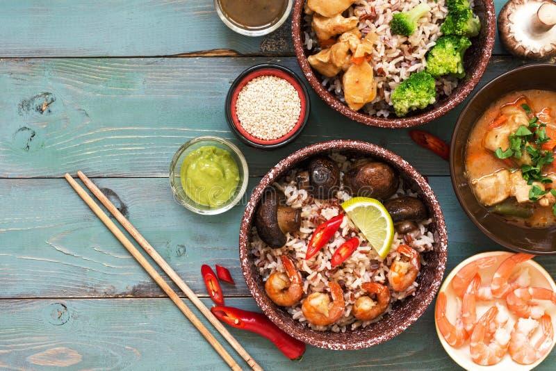 ασιατικά τρόφιμα Γαρίδες, ρύζι, μανιτάρια, μπρόκολο, μαγειρευμένο κοτόπουλο, σάλτσες σε ένα αγροτικό ξύλινο υπόβαθρο Τοπ άποψη, δ στοκ φωτογραφία με δικαίωμα ελεύθερης χρήσης