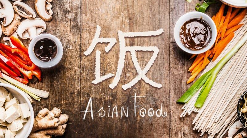 Ασιατικά τρόφιμα με τα διάφορα λαχανικά που μαγειρεύουν τα συστατικά στο ξύλινο υπόβαθρο με κινεζικό hieroglyph των τροφίμων, τοπ στοκ εικόνες