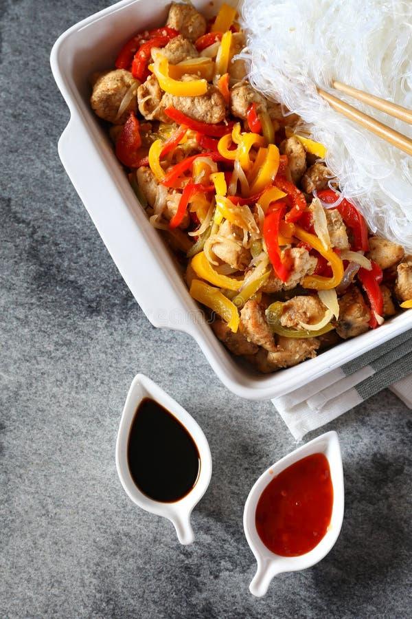 Ασιατικά τρόφιμα: τηγανισμένο κοτόπουλο με τα πιπέρια κουδουνιών tricolor και το ρύζι VE στοκ φωτογραφία