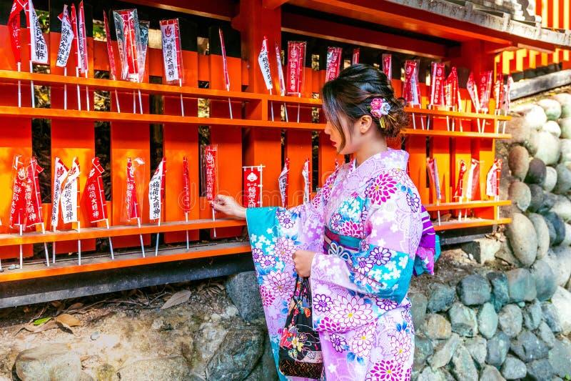 Ασιατικές γυναίκες που φορούν το ιαπωνικό παραδοσιακό κιμονό που επισκέπτεται τον όμορφο στη λάρνακα Fushimi Inari στο Κιότο, Ιαπ στοκ εικόνα