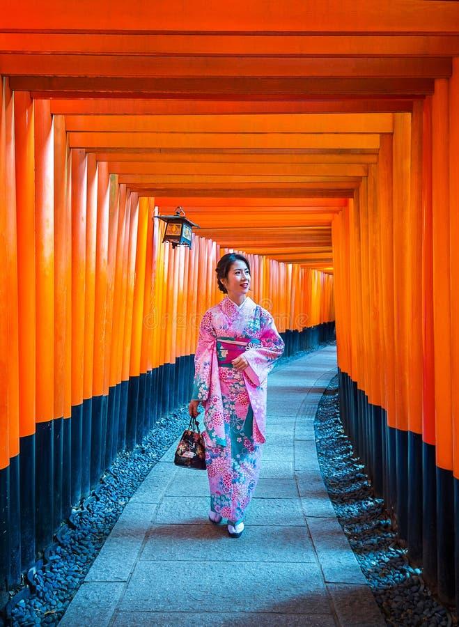 Ασιατικές γυναίκες στα παραδοσιακά ιαπωνικά κιμονό στη λάρνακα Fushimi Inari στο Κιότο, Ιαπωνία στοκ φωτογραφίες