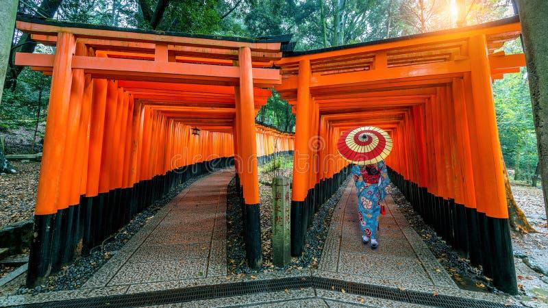 Ασιατικές γυναίκες στα παραδοσιακά ιαπωνικά κιμονό στη λάρνακα Fushimi Inari στο Κιότο, Ιαπωνία στοκ εικόνες