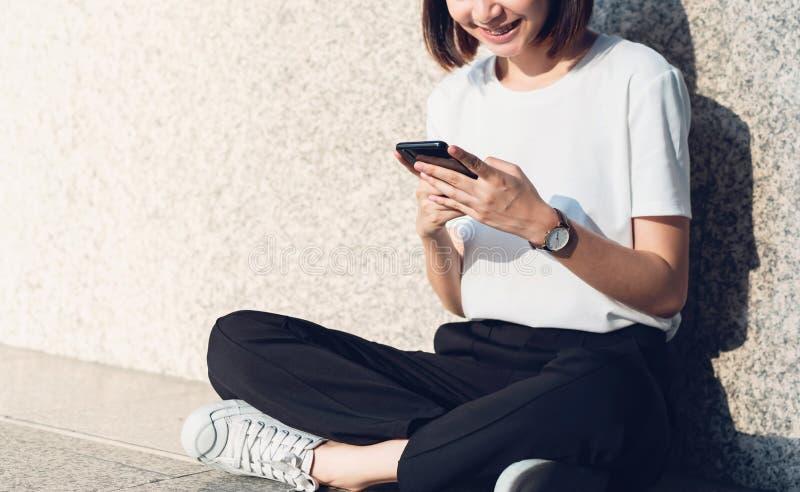 Ασιατικές γυναίκες της ευτυχούς συνεδρίασης χαμόγελου που χρησιμοποιεί το smartphone στοκ φωτογραφία με δικαίωμα ελεύθερης χρήσης