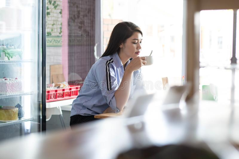 Ασιατικές γυναίκες Attracive που απολαμβάνουν τον καφέ πρωινού της στο κατάστημα κέικ μόνο στοκ φωτογραφία με δικαίωμα ελεύθερης χρήσης