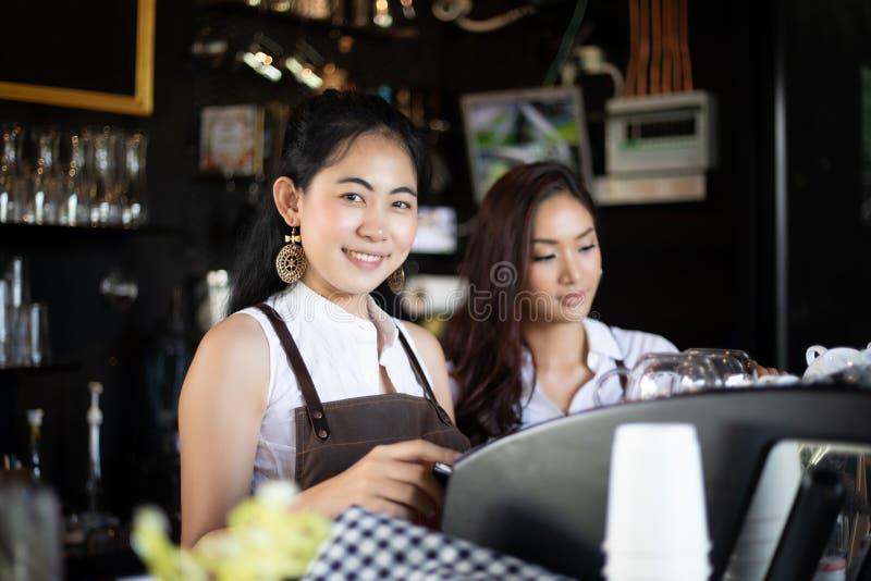 Ασιατικές γυναίκες Barista που χαμογελούν και που χρησιμοποιούν τη μηχανή καφέ στον καφέ s στοκ φωτογραφία