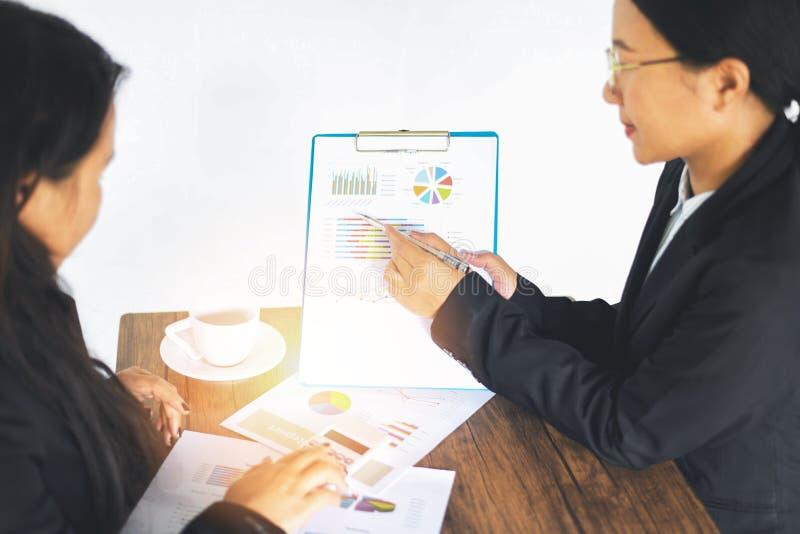 Ασιατικές επιχειρησιακές γυναίκες που απασχολούνται στο παρόν οι οικονομικές πληροφορίες γραφικών παραστάσεων εκθέσεων στη συνεδρ στοκ εικόνες